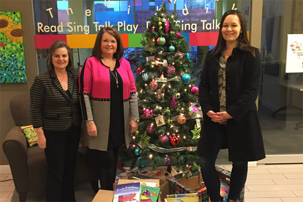 Calgary staff stands around a Christmas tree