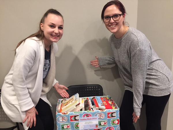 Toronto staff standing next to a box of books